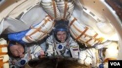 Tiga astronot tersenyum lebar sesaat setelah kapsul Soyuz mendarat dengan sukses di dekat kota Arkalyk, utara Kazakhstan (22/11). Dari kiri : Astronot Amerika Michael Fossum, Kosmonot Rusia Sergei Volkov dan Astronot Jepang Satoshi Furukawa.