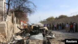 People look at the scene of a suicide attack next to the gate of the Presidential Palace in Mogadishu February 21, 2014. Al Qaeda-linked militants al Shabaab attacked the Somali presidential palace compound on Friday, blasting through a gate with a car bo