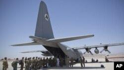 In this Aug. 18, 2015 photo, កងទ័ពជាតិអាហ្ចហ្គានកំពុងតម្រង់ជួរដើម្បីឡើងយន្តហោះ C-130 Hercules នៅមូលដ្ឋានទ័ពអាកាស Kandahar ក្នុងទីក្រុង Kandahar ប្រទេសអាហ្វហ្គានីស្ថានកាលពីថ្ងៃទី១៨ សីហា ២០១៥។