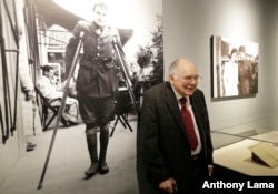 "Patrick Hemingway son of Ernest Hemingway, stands near a 1918 photograph of his father on crutches in Italy while recovering from war wounds during World War I, left, as he visits the exhibit: ""Ernest Hemingway: Between Two Wars"" at the John F. Kennedy Pr"