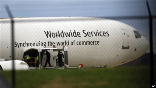 Investigators are seen with a United Parcel Service jet near the company's facility at Philadelphia International Airport, Friday, Oct. 29, 2010.