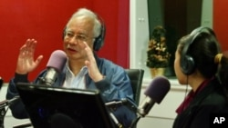 Malaysian Prime Minister Najib Razak, left, gestures as he speaks at a radio station in Kuala Lumpur, Malaysia, September 20, 2011.