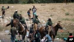 U.S. Customs and Border Protection mounted officers attempt to contain migrants as they cross the Rio Grande from Ciudad Acuña into Del Rio, Texas, Sept. 19, 2021.