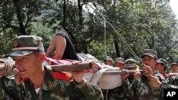 7일 중국 남서부 윈난성 지진현장에 투입된 중국 공안들이 부상자를 옮기고 있다.