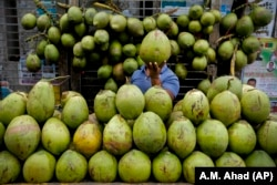 A Bangladeshi street vendor sells coconut on a street in Dhaka, Bangladesh, 2016. (AP Photo/ A.M. Ahad)