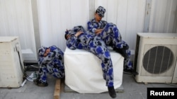 Security personnel take a nap behind one of the halls of Auto China 2016 auto show in Beijing April 25, 2016.