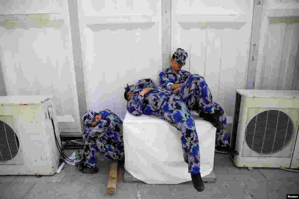Security personnel take a nap behind one of the halls of Auto China 2016 auto show in Beijing.