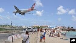 Máy bay hạ cánh tại sân bay quốc tế Princess Juliana trong khi du khách tắm biển và ngắm máy bay trên đảo St. Maarten thuộc lãnh thổ của Hà Lan ở Caribe hôm 13/7. Một khách du lịch người New Zealand đã chết vì sức mạnh của lực đẩy từ phản lực cơ của một máy bay khi cất cánh ở đây.
