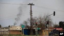 Asap tampak mengepul setelah serangan Turki terhadap militan Kurdi di dekat perbatasan Turki dengan Suriah, Minggu (14/2).