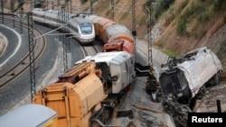 Sebuah kereta api penumpang melintasi kereta naas yang masih teronggok di sisi rel kereta api dekat stasiun di Santiago de Compostela, Spanyol Utara (27/7).
