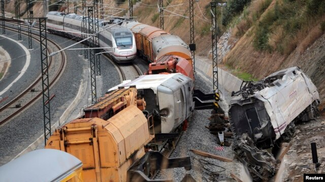 A passenger train drives past the site of a train crash, with the train engine (R) derailed from the track, in Santiago de Compostela, northwestern Spain, July 27, 2013.
