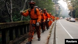 A firefighting crew walk along a road after being deployed to contain a wildfire in Big Sur, California, Dec. 16, 2013.