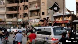 សមាជិកក្រុម Islamic State in Iraq and the Levant (ISIL) គ្រវីទង់ ISIL ខណៈដែលពួកគេបើករថយន្តក្នុងក្រុង Raqqa ប្រទេសអ៊ិរ៉ាក់កាលពីថ្ងៃទី២៩ខែមិថុនាឆ្នាំ២០១៤។