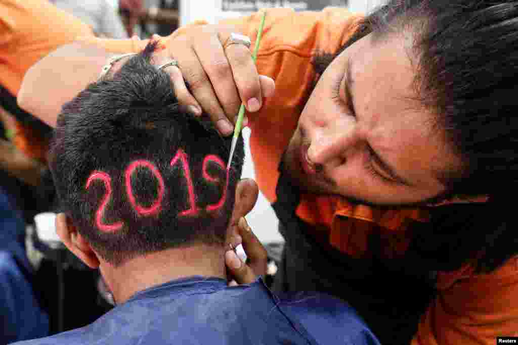 "A man applies color to a haircut with  ""2019"", to welcome the new year at a barbershop in Ahmedabad, India."