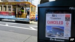 A newspaper headline announcing the closure of large events is displayed as a cable car goes down California Street on March 13, 2020, in San Francisco. (AP Photo/Eric Risberg)