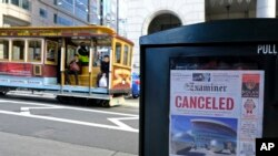 A newspaper headline announcing the closure of large events is displayed as a cable car goes down California Street in San Francisco.