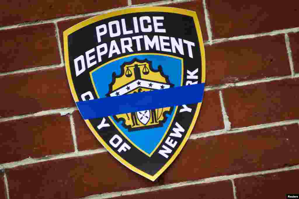 An NYPD logo is pictured on wall above makeshift memorial at the site where two police officers were shot in the head in the Brooklyn borough of New York, Dec. 22, 2014.