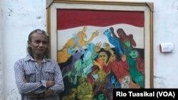 """Jitno Slamet """"Gerbong"""" berpose di depan lukisan karyanya dalam pameran bertajuk """"Indonesia Rakyat"""" di Gang Citra, Cicendo, Bandung, Kamis (23/8/2018) siang. (Foto: Rio Tuasikal/VOA)"""