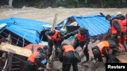Polisi paramiliter mencari orang-orang yang hilang di lokasi tanah longsor di Sanming, provinsi Fujian, China (8/5).