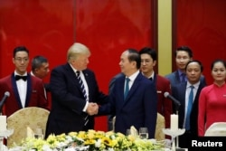 Vietnam's President Tran Dai Quang welcomes U.S. President Donald Trump with a state banquet at the International Convention Center in Hanoi, Nov. 11, 2017.