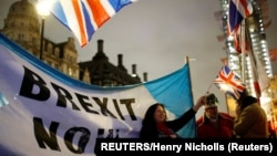 United Kingdom, London, A woman waves a British flag on Brexit day in London