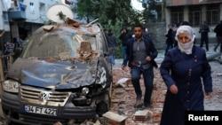 Pyeton kap pase tou pre yon machin ki domaje apre yon eksplozyon nan Diyarbakir, Latiki, 4 Nov. 2016.