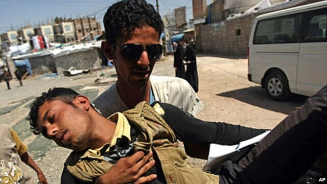 A wounded Yemeni man is carried by a comrade into a makeshift hospital in Sana'a October 23, 2011.