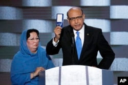 FILE - Khizr Khan, father of fallen U.S. Army Capt. Humayun S. M. Khan, holds up a copy of the Constitution of the United States as his wife, Ghazala, listens during the final day of the Democratic National Convention in Philadelphia , July 28, 2016.