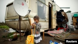 FILE - A girl leans on a school back pack outside a caravan at an encampment of Roma families in Triel-sur-Seine, near Paris, France.