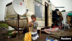 FILE - A girl leans on a school back pack outside a caravan at an encampment of Roma families in Triel-sur-Seine, near Paris, France.