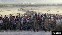 2014年9月18日,大批叙利亚人在土耳其的叙吕奇镇边界线外等待进入,土耳其士兵一旁监视把守。