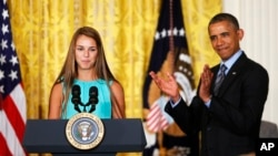President Barack Obama applauds Victoria Bellucci, a 2014 graduate of Huntingtown High Shool in Huntingtown, Maryland, who suffered five concussions playing soccer, May 29, 2014.