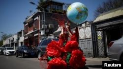"""一名藝術家在北京的藍天下慶祝""""地球日""""。(2020年4月22日)"""