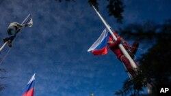 សមាជិកម្នាក់នៃកងកម្លាំងការពារខ្លួនដែលគាំទ្រប្រទេសរុស្ស៊ីទម្លាក់ទង់កងទ័ពជើងទឹកអ៊ុយក្រែនខណៈដែលម្នាក់ទៀតបង្ហូតទង់ជាតិរុស្ស៊ី នៅឯបញ្ជាការដ្ឋានកងទ័ពជើងទឹកអ៊ុយក្រែននៅទីក្រុង Sevastopol ឧបទ្វីបគ្រីមា កាលពីថ្ងៃទី១៩ ខែមីនា ឆ្នាំ២០១៤។
