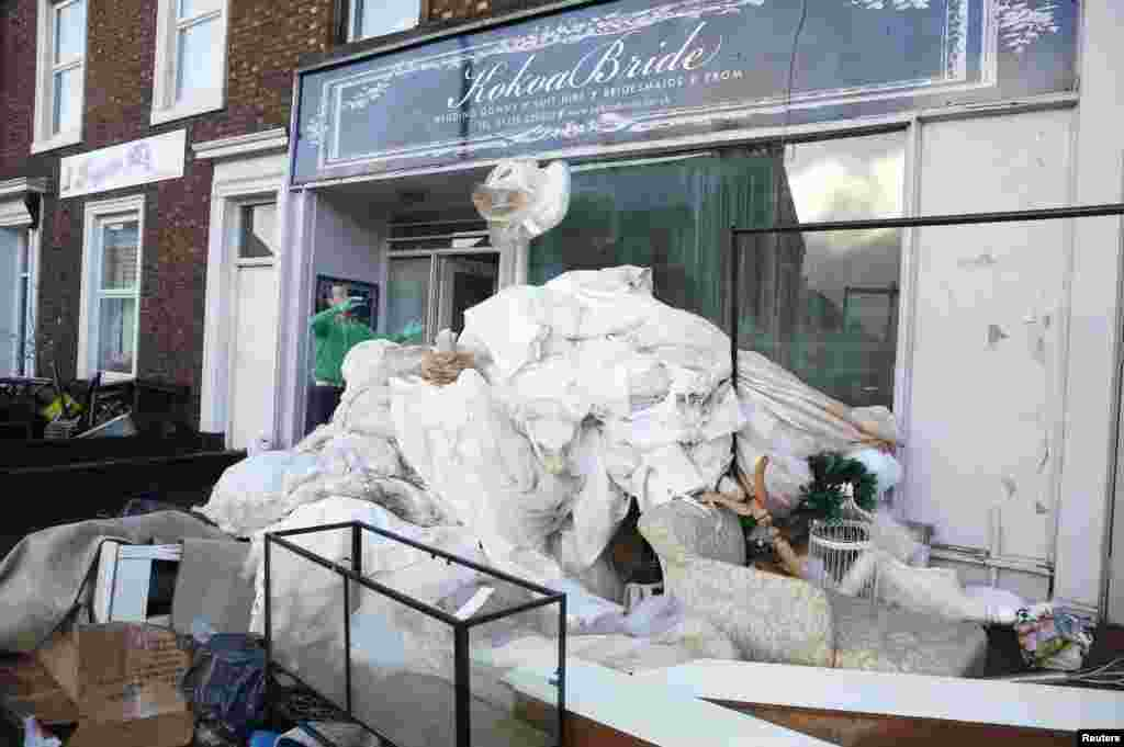 A man throws out flood-ruined stock from a wedding clothing business in Carlisle, northern England.