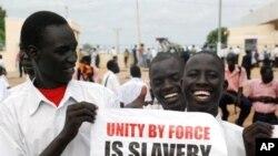 """چهند هاوڵاتیـیهکی باشوری سودان دروشمێـکیان بهرزکردۆتهوه و لهسهری نوسراوه """"یهکێتیـیهکی به زۆر کۆیلهداریـیه""""، چوارشهممه 6 ی دهی 2010"""
