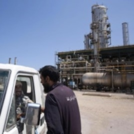 A Libyan worker chats with two rebels in a vehicle as they patrol an oil refinery controlled by anti Gadhafi forces on the western outskirt of Zawiya city, Libya, August 19, 2011