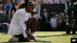 FILE - Serena Williams of the United States kneels after losing a point to Germany's Angelique Kerber during their women's singles final match at the Wimbledon Tennis Championships, in London, July 14, 2018. (AP Photo/Tim Ireland)