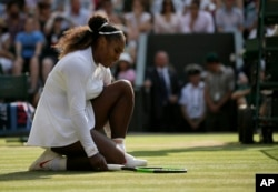 Serena Williams of the United States kneels after losing a point to Germany's Angelique Kerber during their women's singles final match at the Wimbledon Tennis Championships, in London, July 14, 2018.
