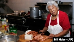 "FILE - In this Jan. 20, 2009, file photo, Chef Leah Chase, owner of Dooky Chase' prepares for lunch at her restaurant in New Orleans. Chase was lovingly known as the ""Queen of Creole Cuisine."" (AP Photo/Bill Haber, File)"
