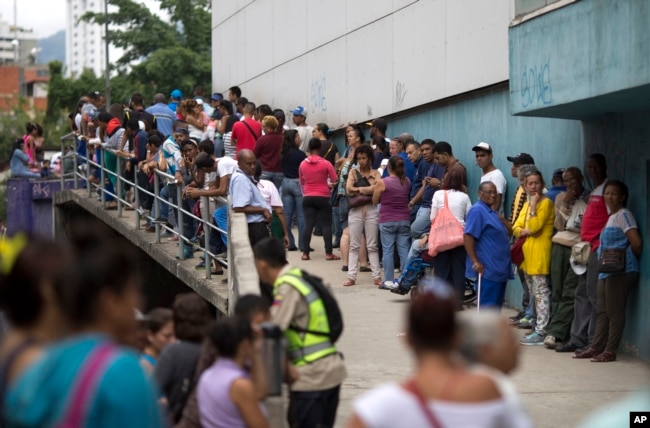 FILE - People wait outside a supermarket to buy government subsided food in Caracas, Venezuela, Nov. 18, 2016.