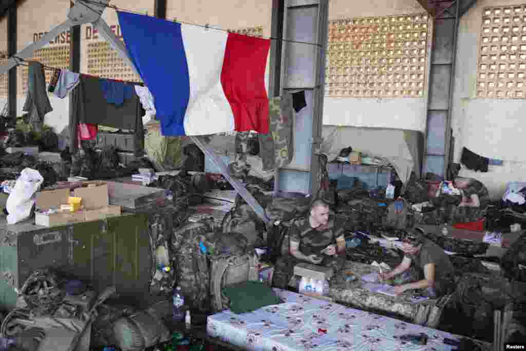 French soldiers talk under a French flag in a hangar at the Malian army air base in Bamako, January 14, 2013.