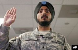 FILE - U.S. Army Spc. Simran Lamba takes the oath of citizenship to become a naturalized citizen before his graduation from basic training at Fort Jackson, South Carolina, Nov. 10, 2010. Updated Pentagon guidelines now make it harder for foreign-born military recruits to qualify for expedited U.S. naturalization.