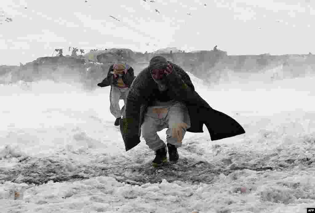 بازماندگان بهمن در منطقه پريان از ايالت پنجشير در شمال کابل، کمکهای امدادی ارتش را از يک هليکوپتر نظامی دريافت میکنند.