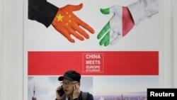 """2019 年5 月28 日,在中國北京舉行的中國國際服務貿易博覽會上,一名男子在一張寫著""""中國在佛羅倫薩遇見歐洲""""的海報旁邊接聽電話。"""