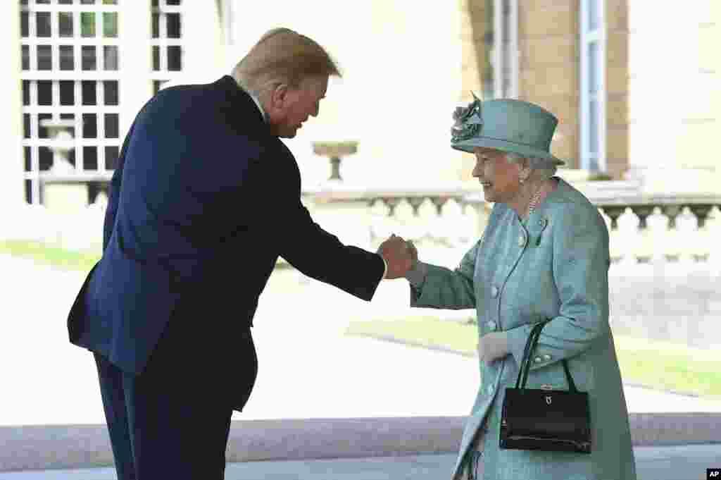 Королева Великобритании Елизавета Вторая приветствует президента США Дональда Трампа в саду Букингемского дворца. 3 июня 2019.