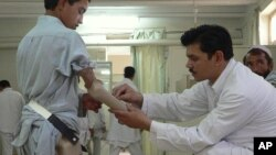 An Afghan technician helps a young amputee adjust his prosthetic arm at one of the International Committee of the Red Cross (ICRC) hospitals for war victims and the disabled in Jalalabad on June 26, 2012.