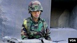 Soldado surcoreano enseña los fragmentos de las armas disparadas por Corea del Norte a la isla fronteriza de Yeonpyeong.