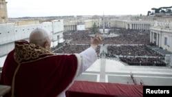 """ພະສັນຕະປະປາເບເນດິກ XVI ໂບກມືໃສ່ ຝູງຊົນໃນຂະນະທີ່ທ່ານ ອວຍພອນໃຫ້ພວກເຂົາເຈົ້າ ໃນການເທດສະໜາng ຫລື """"Urbi et Orbi"""" ທີ່ຈະຕຸລັດ St. Peter. (25 ທັນວາ 2012)"""