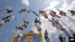 អ្នកគាំទ្រប្រធានាធិបតីយេម៉ែន លោក Ali Abduallah Saleh ឈរលើដងទង់ជាតិក្នុងការអបអរការវិលត្រឡប់របស់លោកមកកាន់ Sanaa ប្រទេសយេម៉ែនវិញ។ ប្រធានាធិបតីរូបនេះ បានធ្វើការវិលត្រឡប់ដ៏គួរឲ្យភ្ញាក់ផ្អើលមួយកាលពីថ្ងៃសុក្រ បន្ទាប់ពីការសម្រាកព្